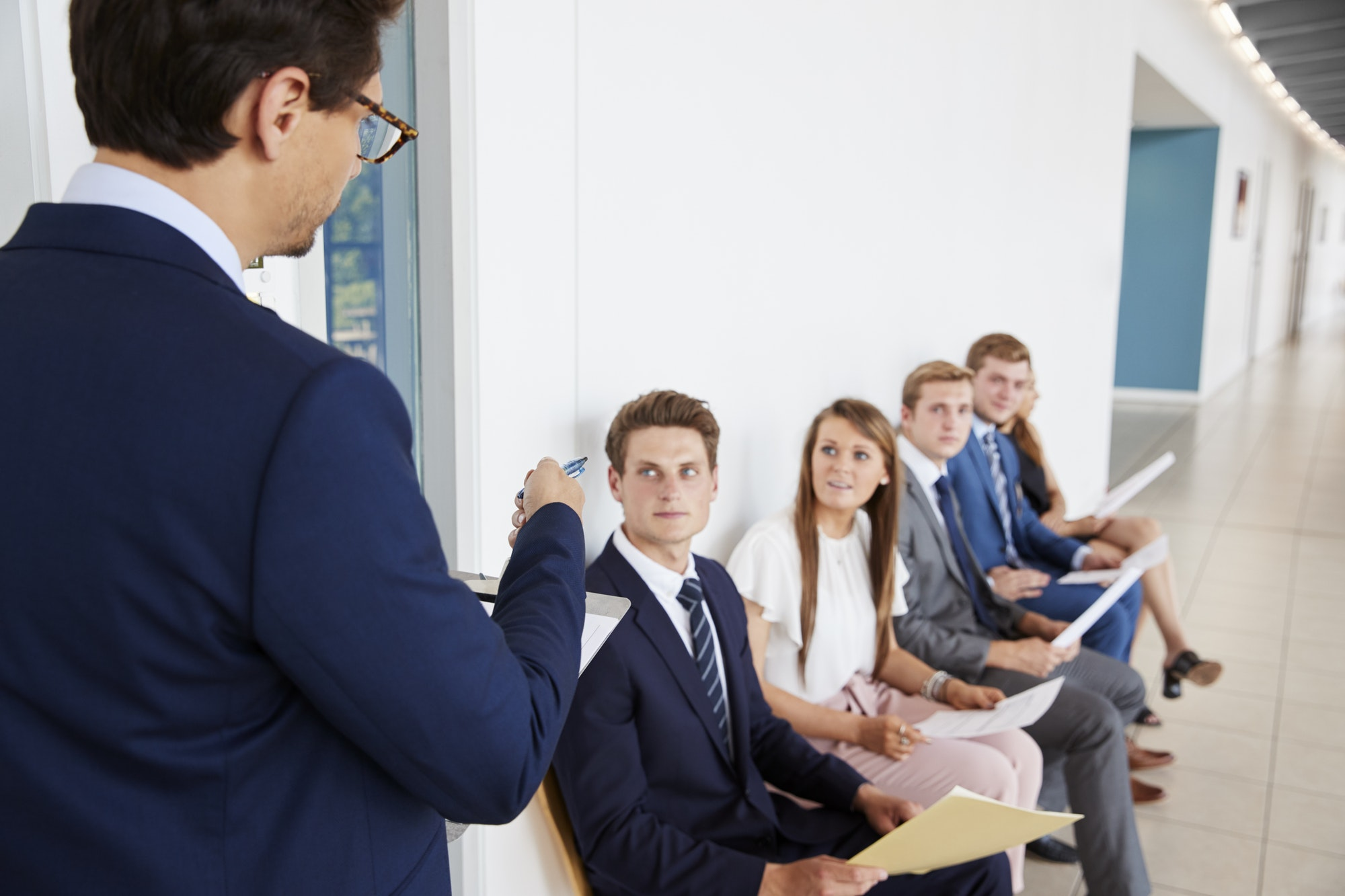 Recruiter addressing job candidates waiting for interviews